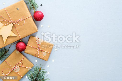 1076063742 istock photo Blue Christmas background with gifts box wrapped kraft paper, fir tree branches, red balls, glitter confetti stars. Christmas, winter, new year concept. Top view with copy space. 1175685111