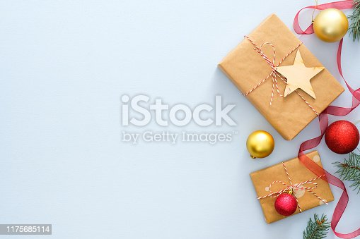 1076063742 istock photo Blue Christmas background with gifts box wrapped kraft paper, fir tree branches, red and golden balls, ribbon. Christmas, winter, new year concept. Top view with copy space. 1175685114