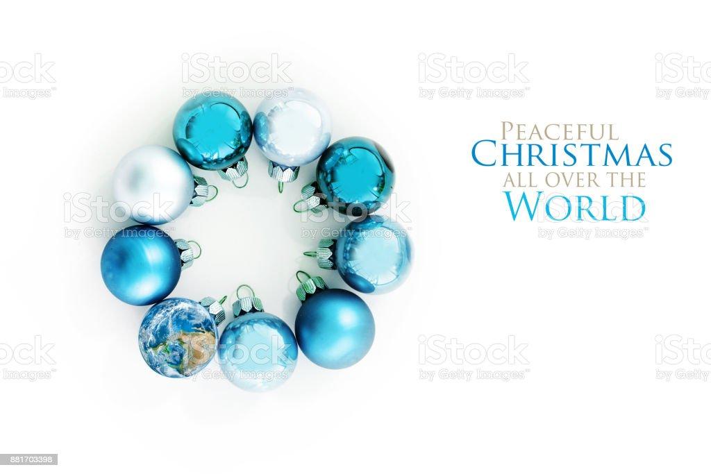 bolas Navidad azules y un globo de tierra en un círculo, aislado con sombras sobre un fondo blanco, tarjeta de felicitación con el texto Navidad pacífica en todo el mundo, uno de los elementos proporcionado por la NASA, tapa plana vista desde arriba - foto de stock