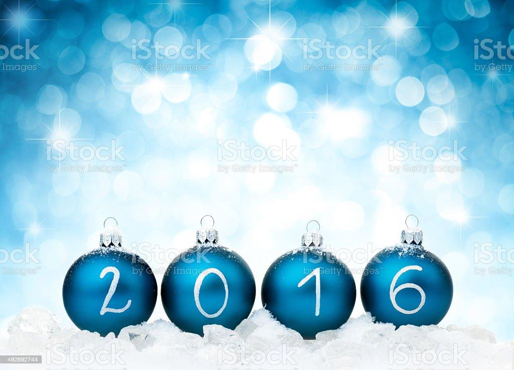 Blue christmas balls arranged in 2016 year against defocused light