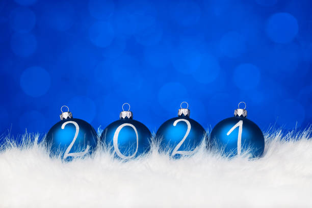 2021 Blue Christmas balls on fur and defocused sparkles stock photo