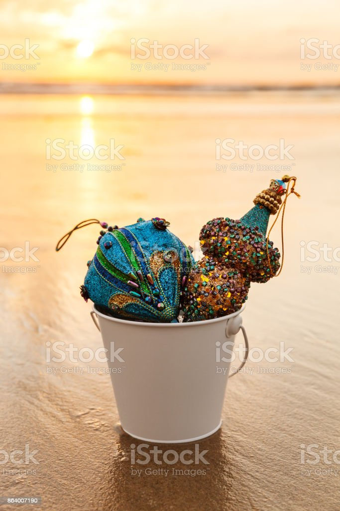 Blue Christmas Decorations collected in a white bucket at Golden Sunset on the Beach stock photo