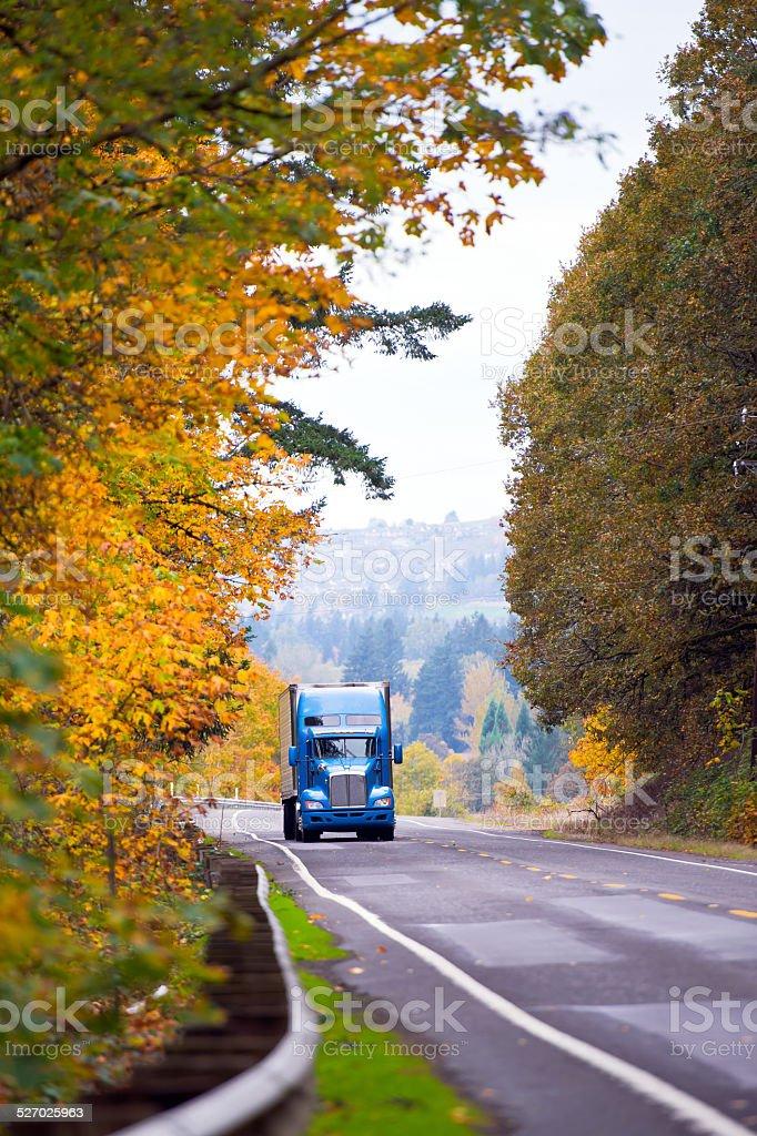 Blue classic modern semi truck on winding autumn road stock photo