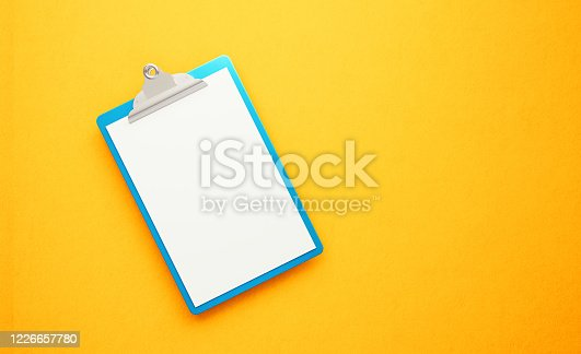 524051315 istock photo Blue Clipboard on Yellow Background 1226657780