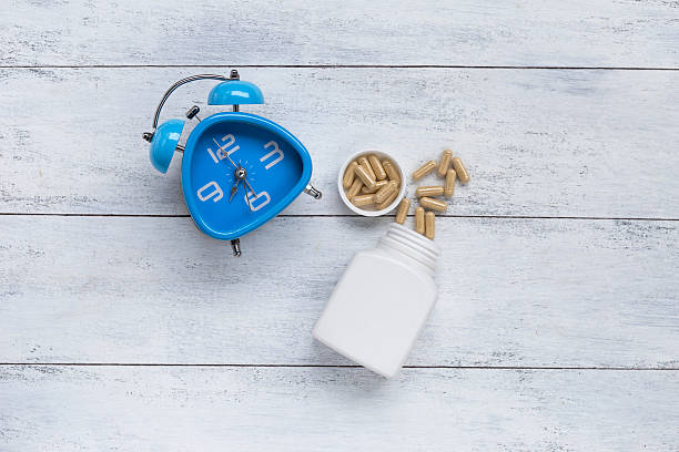 blue clock and herb capsule - sleeping pill stock photos and pictures