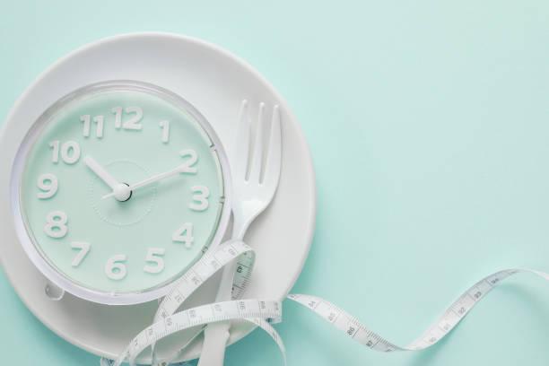 Blaue Uhr auf weißem Teller, Intermittierendes Fastenkonzept, ketogene Ernährung, Gewichtsverlust, Mahlzeit überspringen – Foto