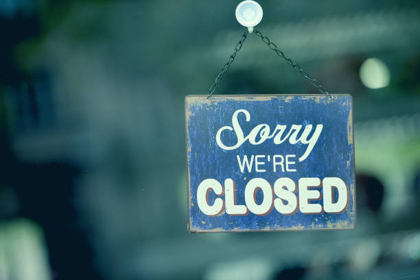"""Blue closed sign in the window of a shop displaying the message """"Sorry we are closed"""" stock photo"""