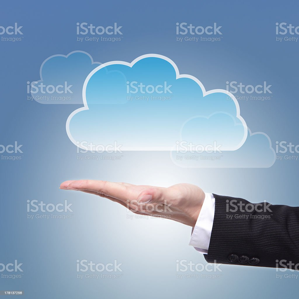Blue cloud hovering above a hand showing a computing concept stock photo