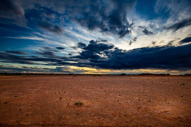 blaue wolken bei sonnenuntergang über harttrockenem rötlich-braunem sahelianland mit verstreuten büschen in der ferne während der regenzeit im sommer außerhalb der niamey-hauptstadt nigers - regenzeit stock-fotos und bilder