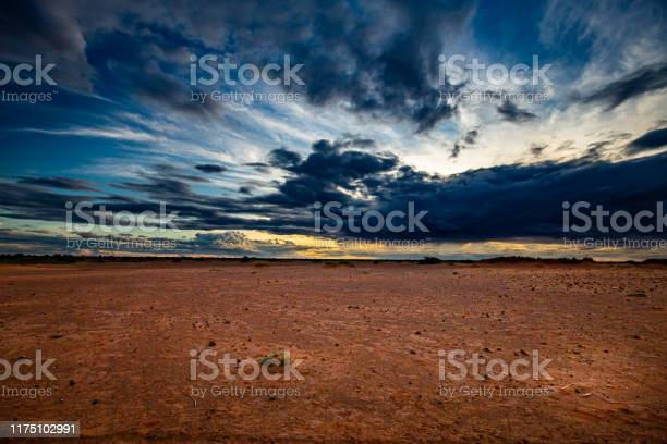 Photo of Blue clouds at sunset over hard dry reddish-brown sahelian land with scattered bushes in the distance during summer rainy season outside Niamey capital of Niger