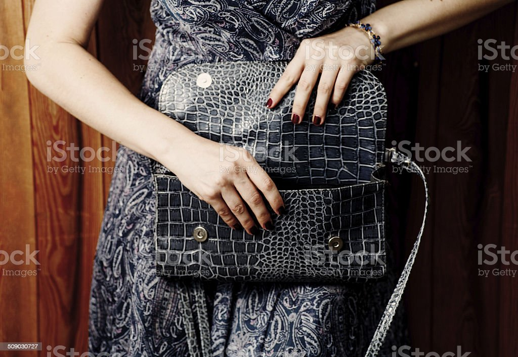 Blue clutch in hands stock photo