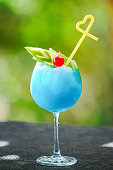 istock Blue cocktail with apple, cherry and yellow straw 1311891129