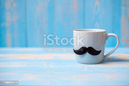 istock Blue coffee cup with Black mustache on wood table background in the morning. Father, International men day, Prostate Cancer Awareness and World cancer day concept 1168853419