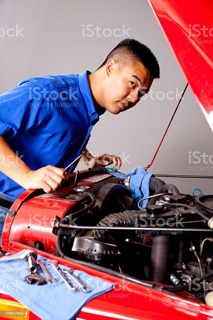 Blue collar Asian mechanic working motor vehicle open hood royalty-free stock photo