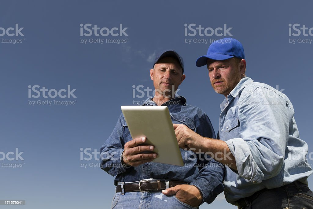 An image of two blue collar workers, farmers or truckers, in...