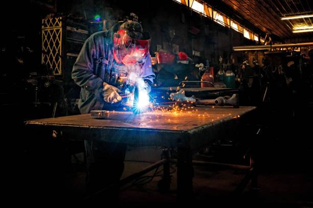 Blue collar Industrial worker welding stock photo