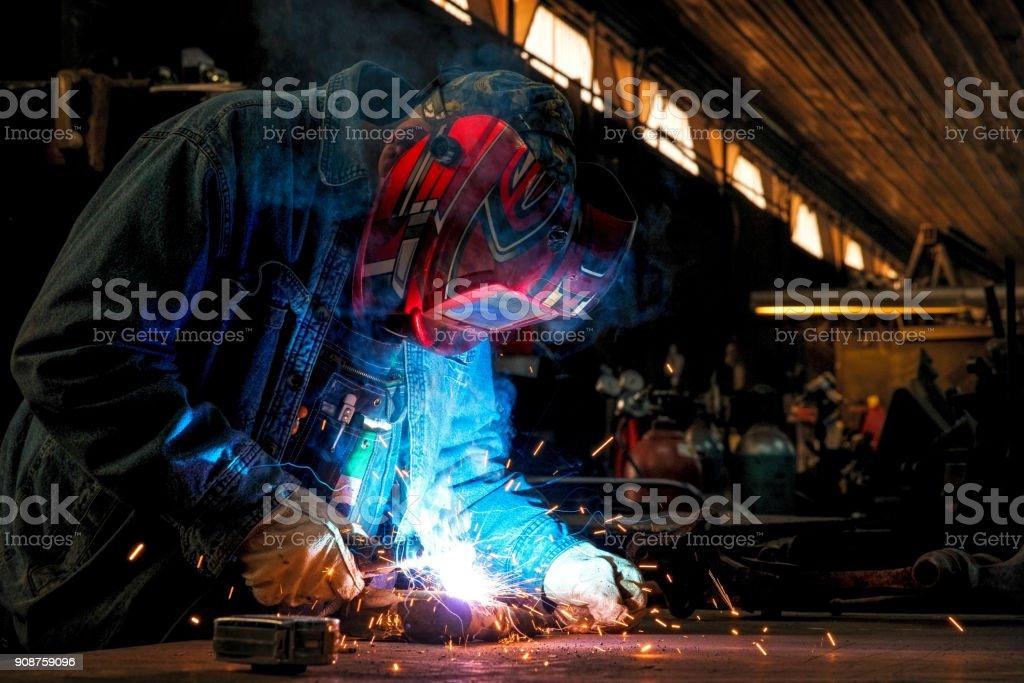 Welders wearing protective gear working in a warehouse