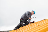 A mid-adult construction worker constructs a roof; he is using a hammer and is wearing a hardhat.