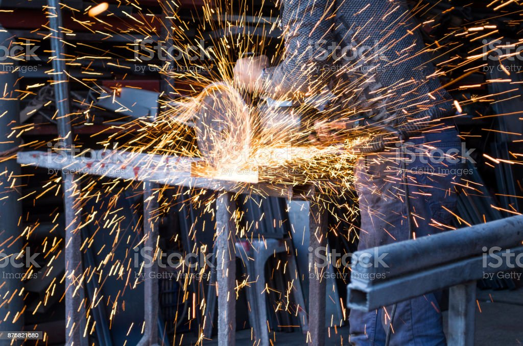 Blue Collar Worker Cutting Steel And making sparks fly stock photo
