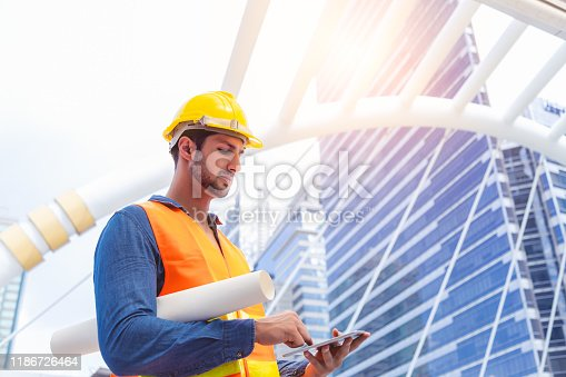Blue collar worker, engineer man work on digital tablet, hold blue print, wear safety hat, stand near worksite. Worker guy survey a land for big project of building or estate. look determined