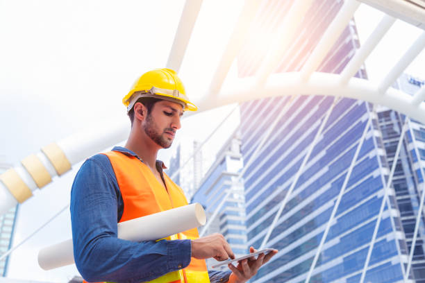 Blue collar worker, engineer man work on digital tablet, hold blue print, wear safety hat, stand near worksite. Worker guy survey a land for big project of building or estate. look determined stock photo