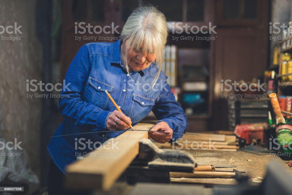 Blue collar worker in workshop measure wood stock photo