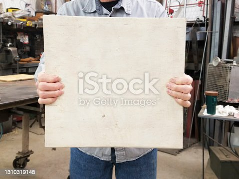 istock Blue Collar worker wearing work gloves holds blank sign ready for you own copy/text. 1310319148