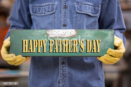 istock Blue Collar worker wearing work gloves holds Happy Father's Day sign. 1307251161
