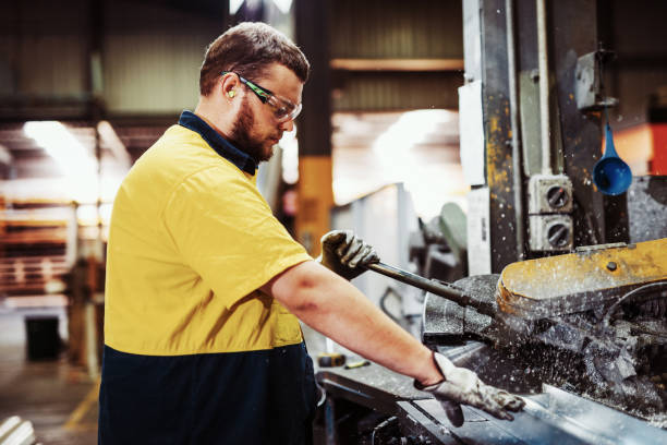 Blue collar workers in industry - grinding and cutting metal bars stock photo
