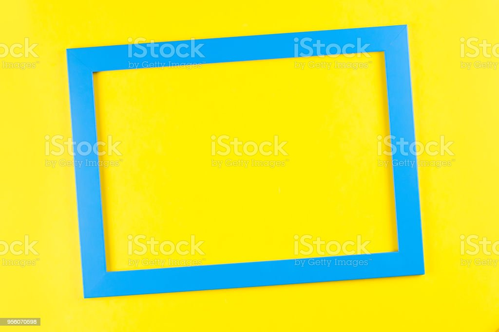 blue color frame on bright yellow background. stock photo