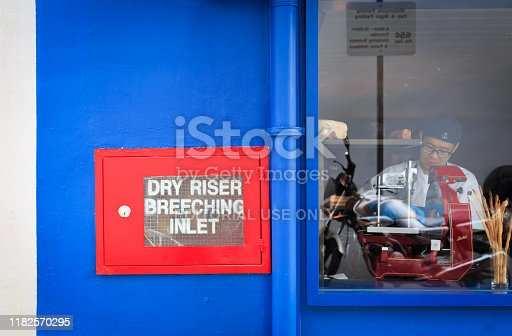 Singapore-14 JUL 2018:blue color restaurant window facade with red dry riser box