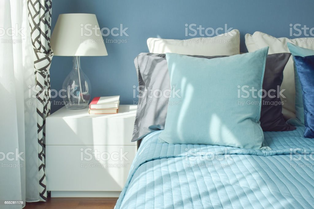 Blue color scheme bedding and white table lamp with natural light from a window stock photo