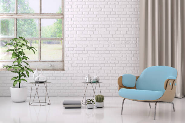 blue colored armchair with coffee table, flowers and blank wall template stock photo