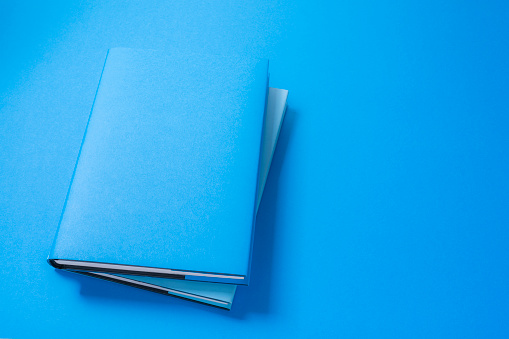 High angle view of a blue colored cover book shot on blue background. High resolution 42Mp studio digital capture taken with SONY A7rII and Zeiss Batis 40mm F2.0 CF lens