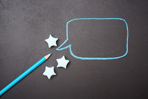 Blue colored pencil  draws rectangular speech bubble with origami stars