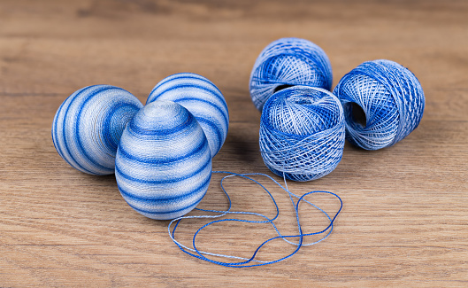 Blue colored striped Easter eggs and cotton yarn in decorative skeins on wooden background