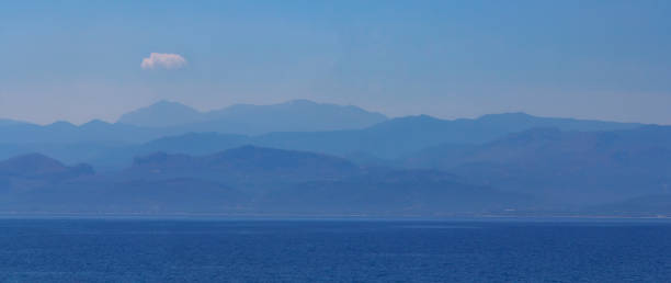 Blue colour of nature. Panorama of beautiful and peacefull Crete landscape with misty silhouettes of blue mountains and calm sea of the Mediterranean stock photo