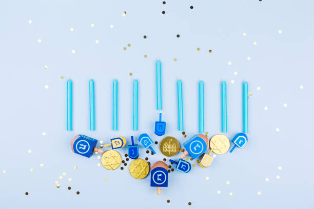blue confetti background with menora made of dreidels and chocolate coins. hanukkah and judaic holiday concept. - hanukkah stock pictures, royalty-free photos & images