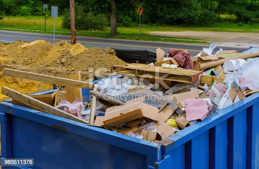 Industrial garbage bin blue construction debris container filled with rock and concrete rubble.