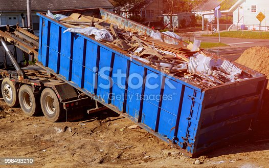 istock Blue construction debris container filled with rock and concrete rubble. Industrial garbage bin 996493210