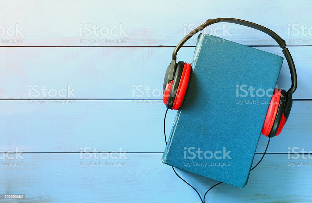 blue cover book and headphones over wooden table stock photo