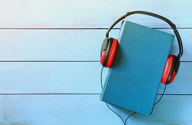 blue cover book and headphones over wooden table - audioutrustning bildbanksfoton och bilder