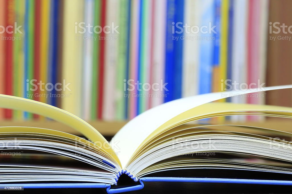 Blue covered book open on library table stock photo