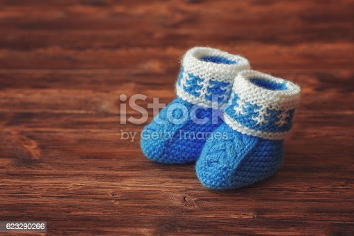 Blue hand made crochet baby booties on wooden background, copyspace, closeup, vintage toned