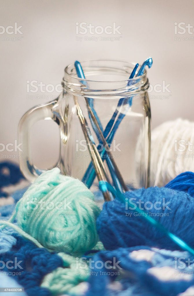 Blue crochet project with hooks in glass royalty-free stock photo