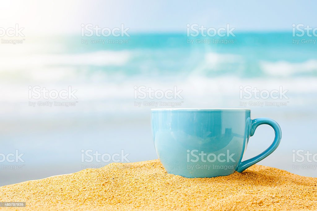 blue cup of coffee on white sand beach stock photo