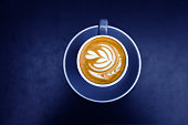 Blue cup of fresh cappuccino with latte art on dark metal table background. Trendy glow bright color. Empty place for text, copy space. Coffee addiction concept. Top view from above.