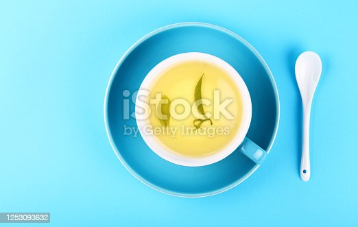 Close up one full cup of green oolong or herbal tea on saucer with white spoon over pastel blue paper background, elevated top view, directly above