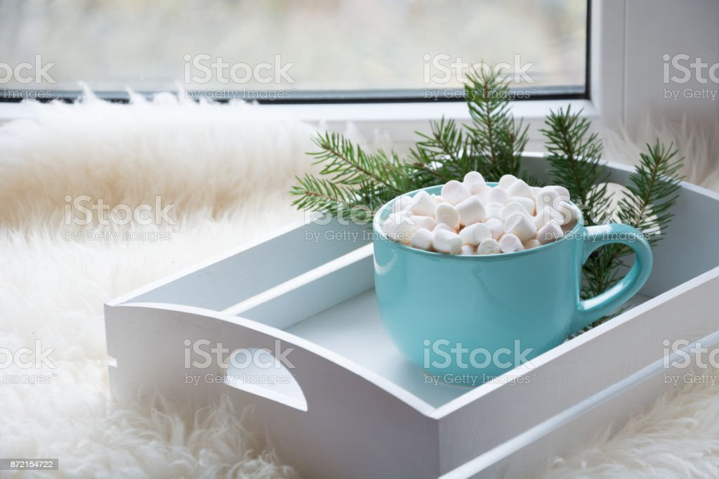 Blue cup of hot chocolate with marshmallow on windowsill. Weekend concept. Home style. Christmas time. stock photo