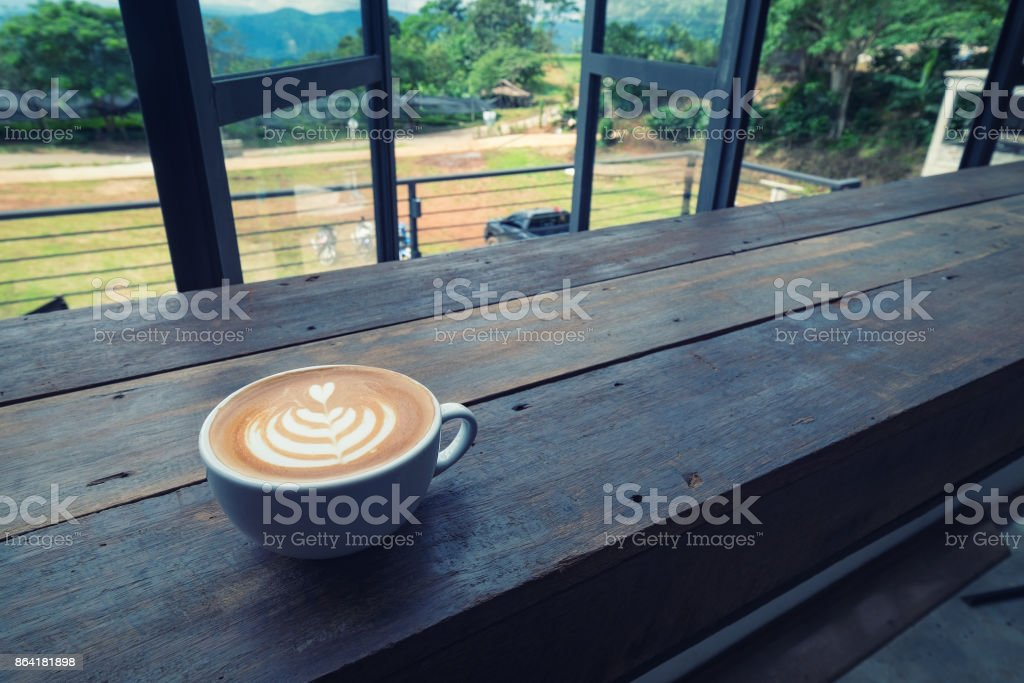 A blue cup of hot latte art coffee on the wooden table in coffee cafe royalty-free stock photo